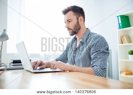 Side View Of Concentrated Man Writing Book On Laptop