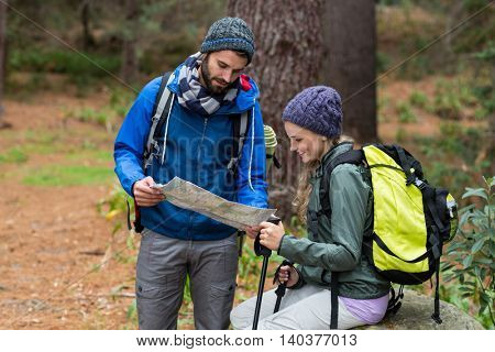 Happy hiker couple looking map at countryside