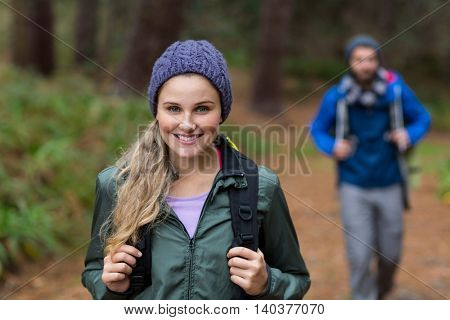 Portrait of beautiful woman while hiking in forest at countryside