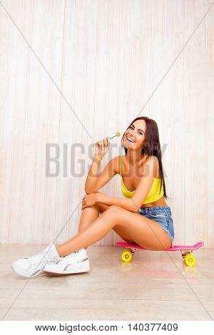 Pretty Woman Licking Lollipop While Sitting On Skateboard