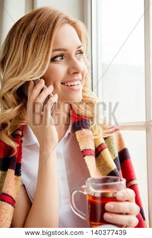 Pretty woman drinking tea and looking in window while talking on phone