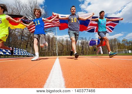 Portrait of four teenage boys, participants of race on racetrack, during international athletics competitions, running with flags of their countries behind them