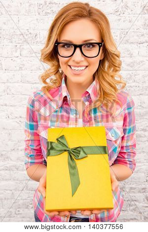 Portrait Of Happy Woman In Glasses Holding Yellow Present