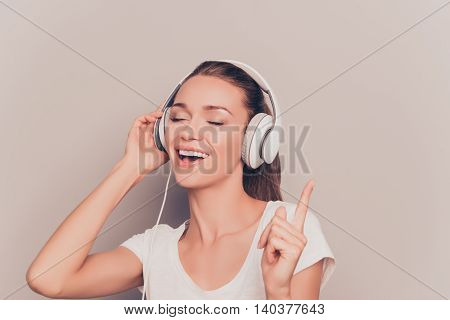 Beautiful Young Woman Listening Music In Headphones And Singing