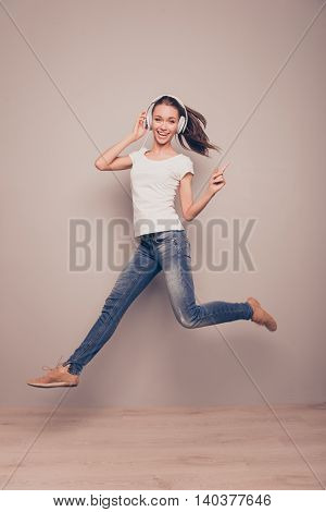 Full Length Portrait Of A Happy Woman Jumping While Listening Music