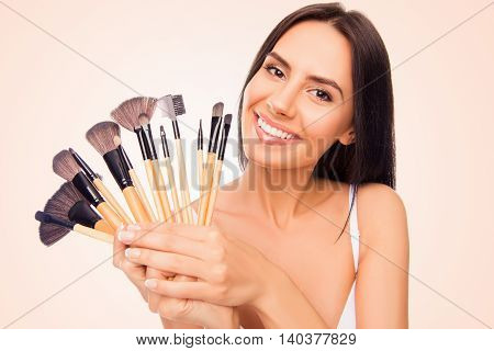 Portrait Of Young Smiling Happy Woman Holding Makeup Brushes