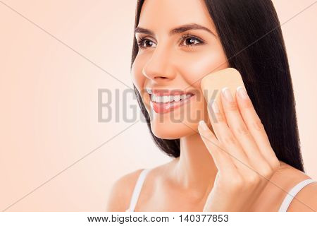 Portrait Of Happy Young Woman With Sponge Doing Professional Make-up