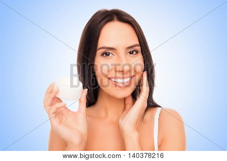 Portrait Of  Pretty Woman Holding Jar And Applying Cream On Her Face
