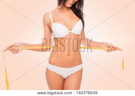 Pretty Girl In White Underwear Measuring Her Waist With Measuring Tape