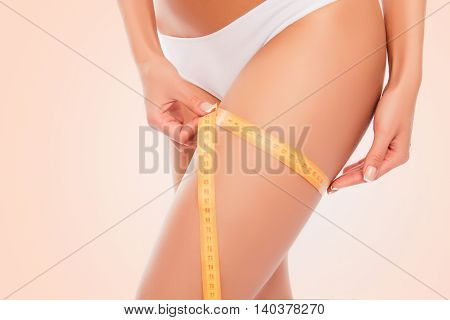 Close Up Photo Of Sexy Woman Measuring Her Leg's Size With Tape Measure