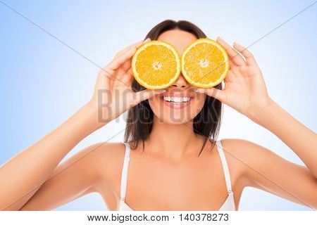 Portrait Of Young Beautiful Woman Holding Orange Near Eyes Like Glasses