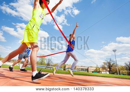 Side view of teenage girl crossing finish line on the racetrack