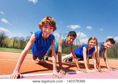 Close-up picture of four happy teenagers in sportswear holding a plank standing in a row  on the track outdoors