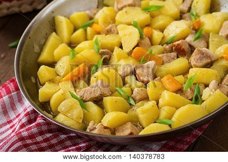Stewed Potatoes With Meat In A Frying Pan On A Wooden Table