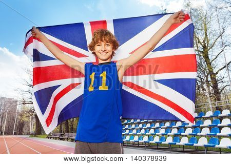 Close-up portrait of happy smiling teenage boy in sportswear holding flag of Great Britain behind him outside in the stadium