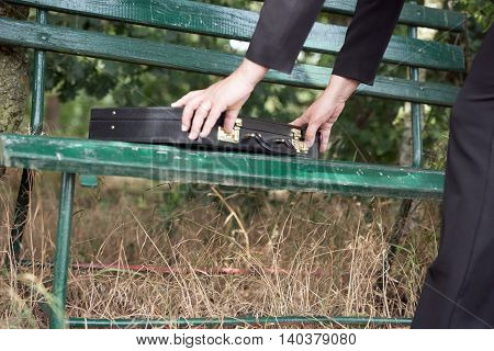 Businesswoman opens briefcase on a park bench