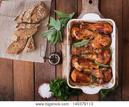 Appetizing Oven Baked Golden Chicken Drumsticks In A Baking Dish On A Wooden Table. Top View