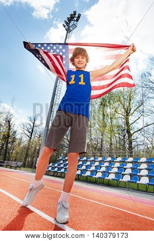 Full-length portrait of happy smiling teenage boy in sportswear, holding American flag behind him, standing on track, bottom view