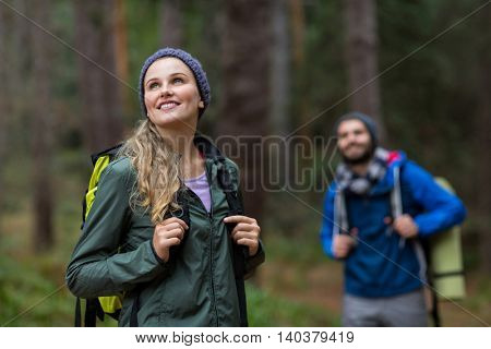 Beautiful woman looking at nature while hiking in forest at countryside