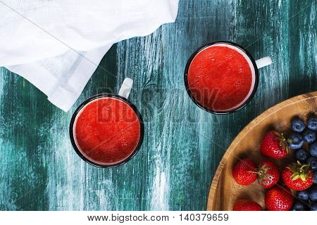Strawberry soup in retro enamel mugs over wooden table