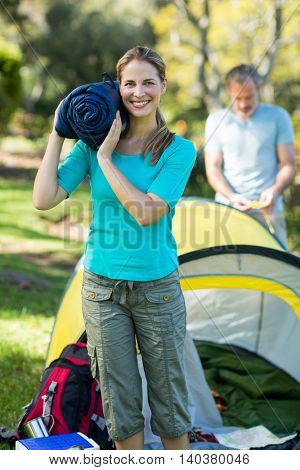 Beautiful female hiker holding travel bed in forest