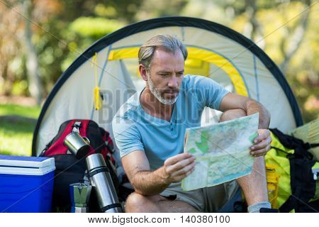 Hiker looking at map in forest