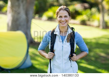 Portrait of female hiker standing with rucksack in forest