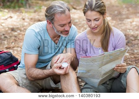 Hiker couple holding compass and reading map in forest