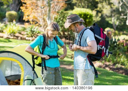Hiker couple wearing strap in forest