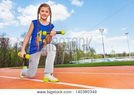 Close-up picture of active teenage girl doing exercises with dumbbells standing on her knee in stadium