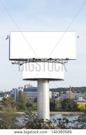 Blank billboards near the river in urban environment