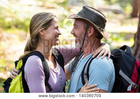 Romantic hiker couple embracing each other in forest