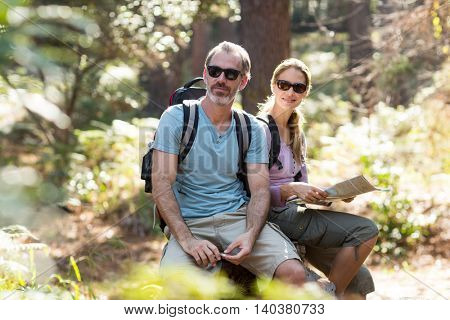 Hiker couple sitting on rock with map in forest