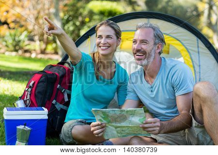 Happy hiker couple holding map and pointing at distance