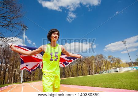 Portrait of teenage sprinter, running with flag of Great Britain outside on the racetrack