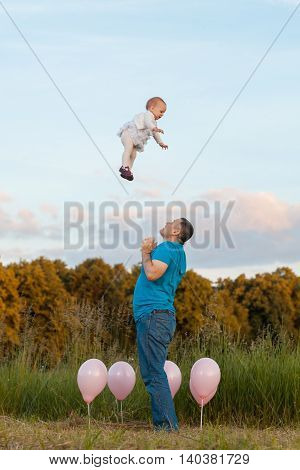 Young man throws up baby girl. They are on a meadow