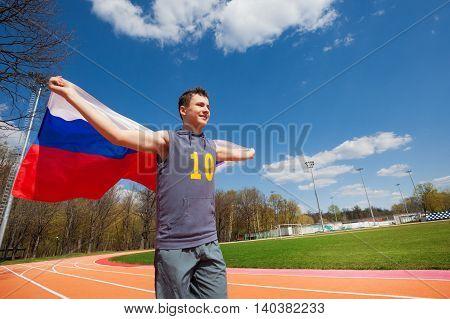 Happy teenage sprinter, boy in sportswear, waving flag of Russian Federation, running on the racetrack