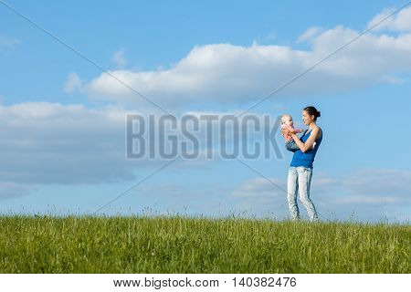 Young mother with her daughter on a green meadow against the sky with clouds