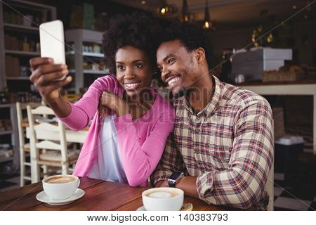 Happy young couple sitting at table taking selfie in cafeteria