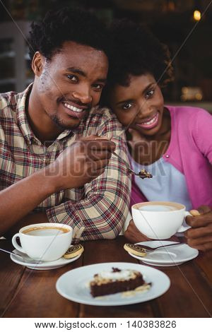 Portrait of happy young couple having breakfast in cafeteria