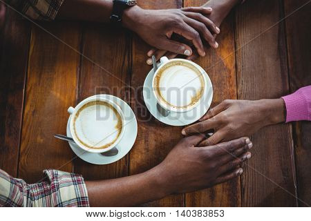 Couple holding hands while having coffee in cafeteria