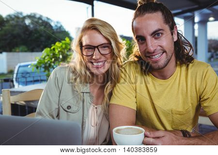 Portrait of happy young couple using laptop while having coffee in cafeteria