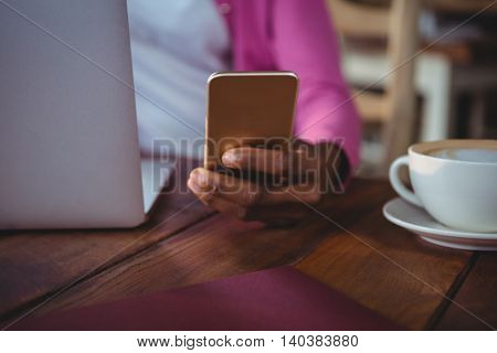 Mid section of woman using mobile phone while having coffee in cafeteria