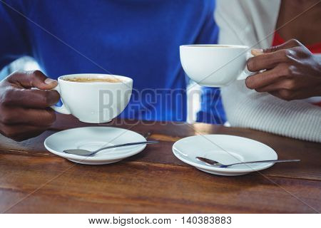 Mid section of couple having coffee in cafeteria