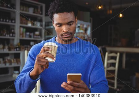 Young man text messaging on mobile phone while having coffee in cafeteria