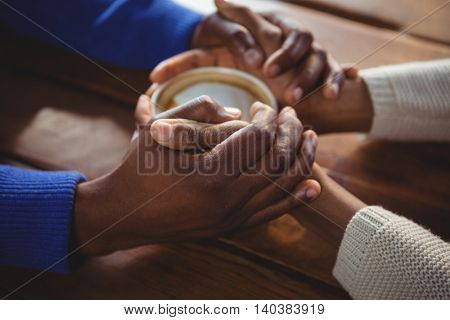 Close-up of couple holding hands while having coffee in cafeteria