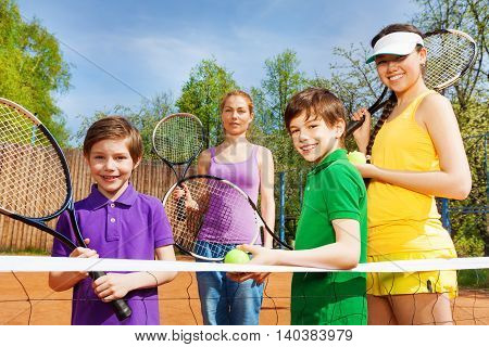 Happy sportive family of four people, standing near tennis net on the clay court with rackets in summer