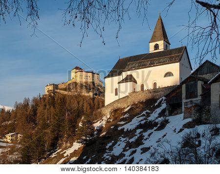 Small rural church and castle on the background in Tarasp village, Graubunden, Switzerland