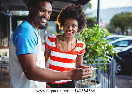 Portrait of smiling couple using mobile phone in cafe