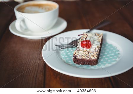 Pastry with whipped cream and cherry topping on plate in cafeteria
